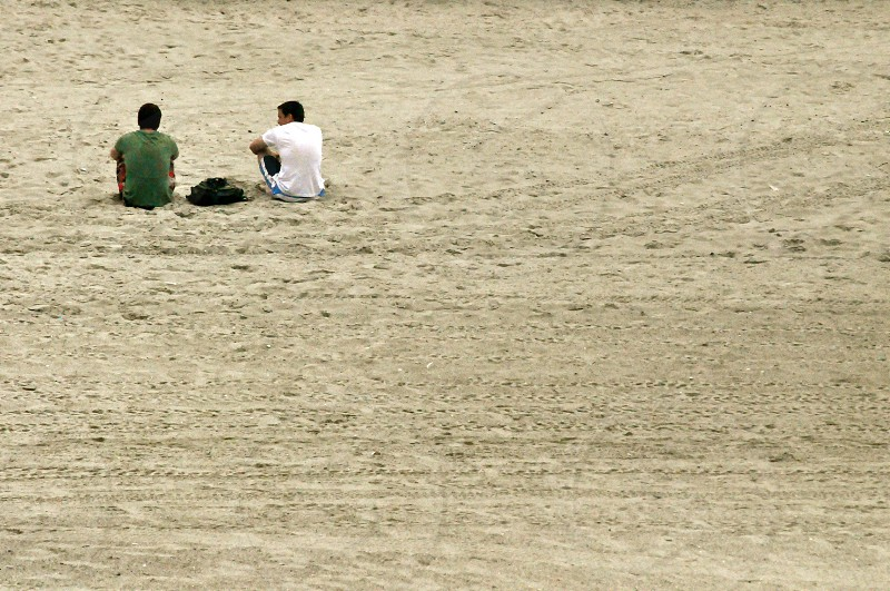 Men talk while sitting on the sand photo