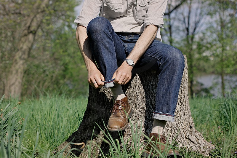 hands man jeans boots roll cuff fold sleeves nature stump grass masculine style photo