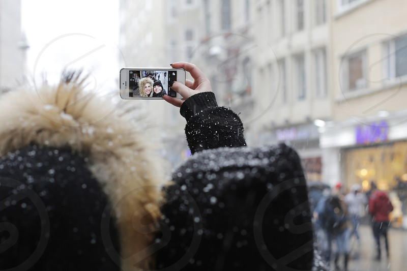 woman holding black iphone taking photo of herself during snow at daytime photo