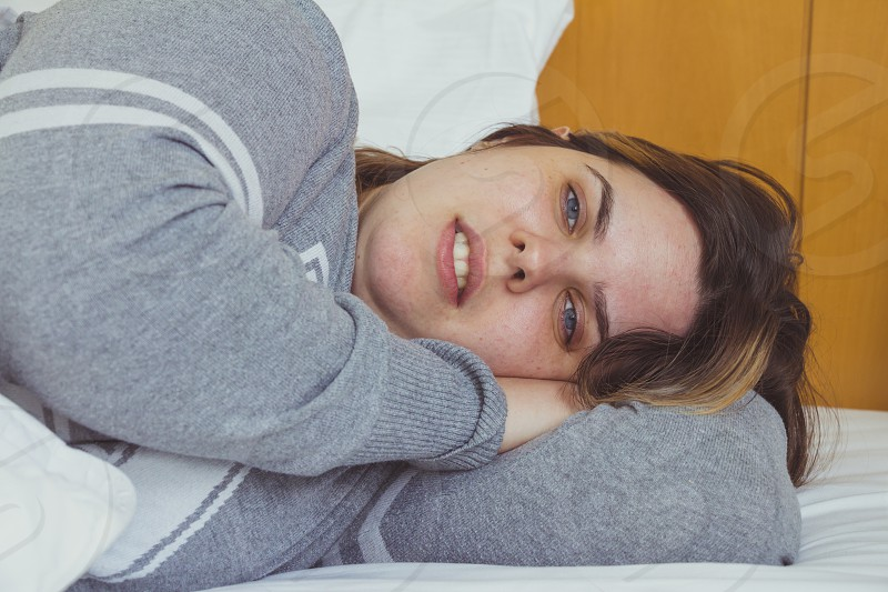 Young woman daydreaming while lying on bed under the blanket. photo