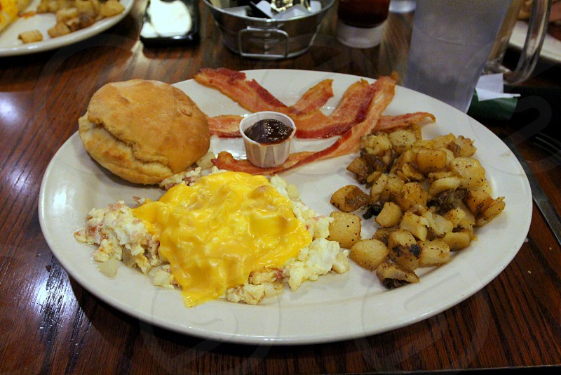 Breakfast plate with cheese covered scrambled eggs hash browns biscuit and bacon photo