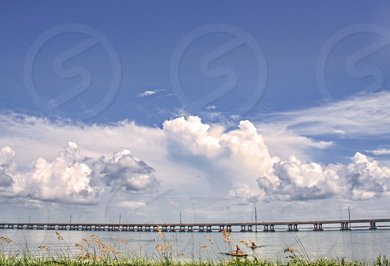A long bridge in the Florida Keys extends over the ocean against a sky with large white clouds. photo