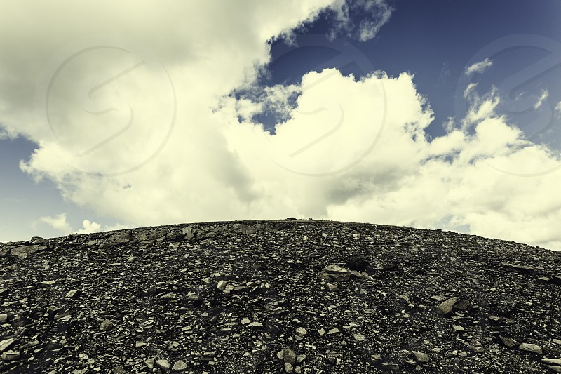 Mountain of stones with blue sky with clouds above photo
