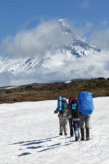 Hiking on Kamchatka Peninsula: group of tourists and travelers with large backpacks behind the shoulders climbing to mountains on background of snow-capped rocky volcanoes on sunny day. photo