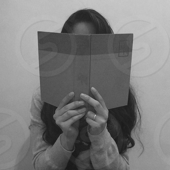 woman in gray long sleeved shirt holding a book photo