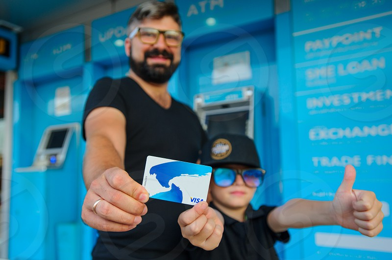 UK ATM. Father and son showing the credit card at the camera photo