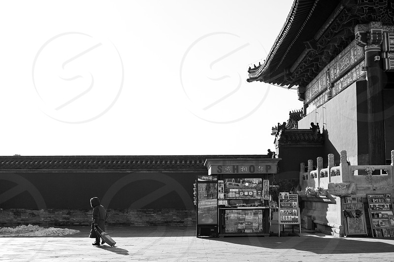 In Beijing a hooded figure walks with a rolling suitcase past a tourist souvenir gift shop next to an ancient Chinese building  photo