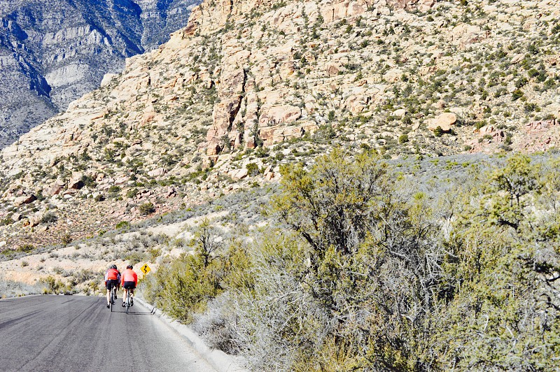 two cyclists in red going down  mountain highway photo