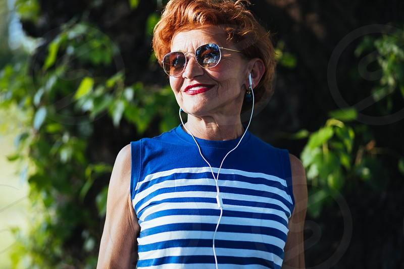 Mature woman listening to the music on headphones in the park photo