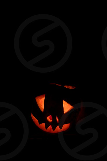 Scary face halloween pumpkin with glowing candle inside isolated on black background  photo