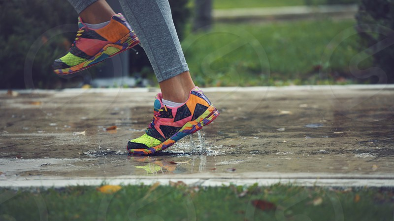 Young woman running on asphalt sports field in rainy weather splashing puddles. photo