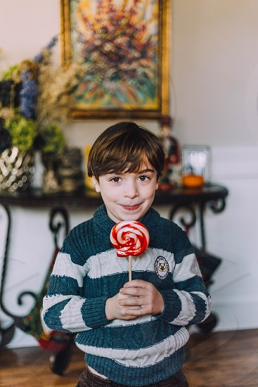 Lollypop toddler boy Christmas sweater winter sticking out tongue photo