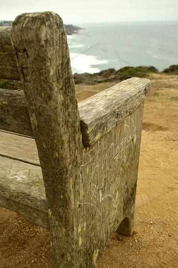 bench on cliffs overlooking ocean photo