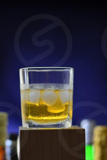 beer on the rock in shot glass on wooden block shallow focus photo