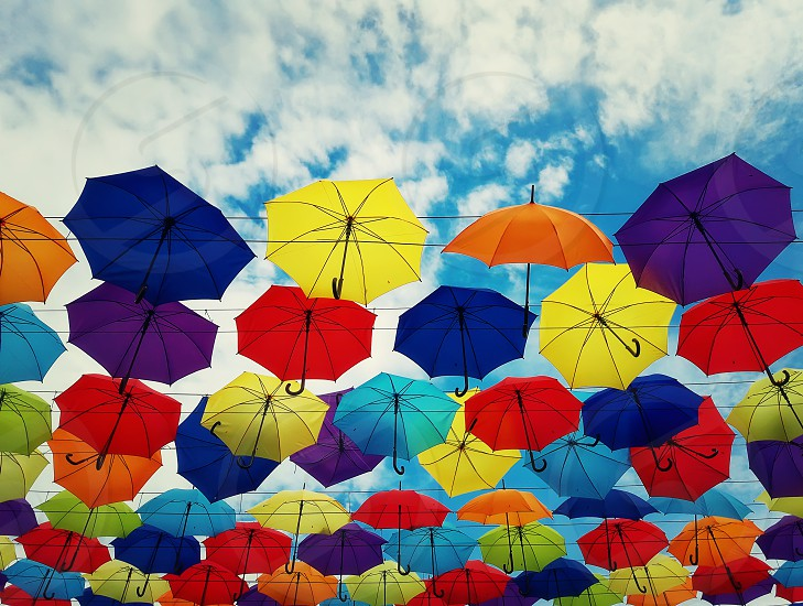 Colorful umbrellas hanging above a city street isolated on blue sky background. Bright urban decoration. photo
