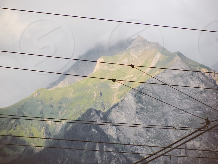 wires clouds mountain vegetation photo