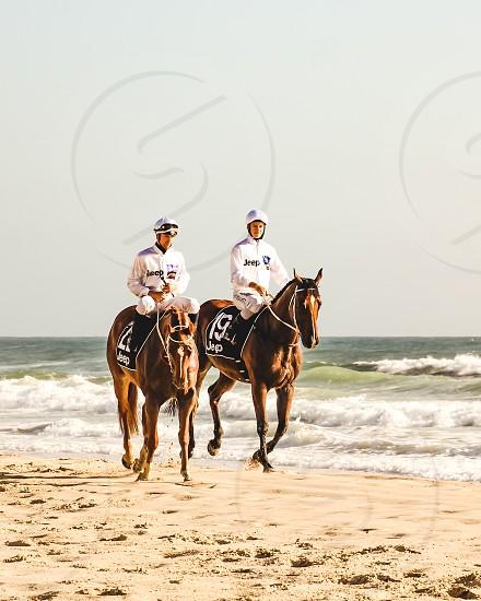 beautiful racehorses and their jockeys strutting along the beach Surfer Paradise Queensland Australia - Jeep Magic Millions  photo