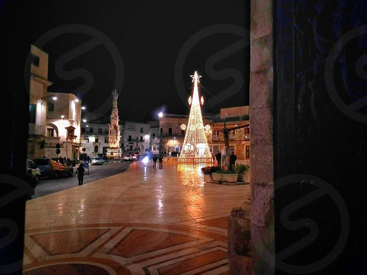 people walking near Christmas decoration during night photo