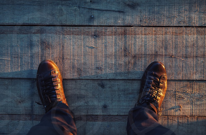 Man is standing on wooden floor view from above. photo