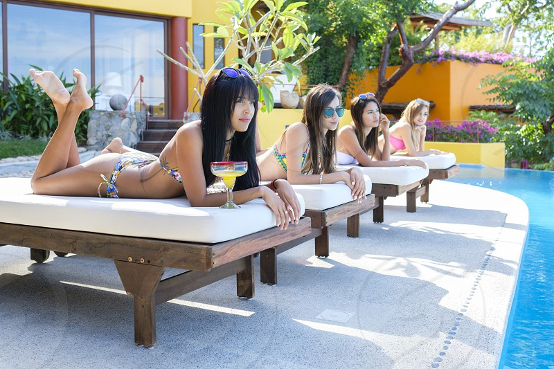 Multiple attractive young women lying on loungers tanning and watching others next to a swimming pool of an upscale residence in Mexico photo