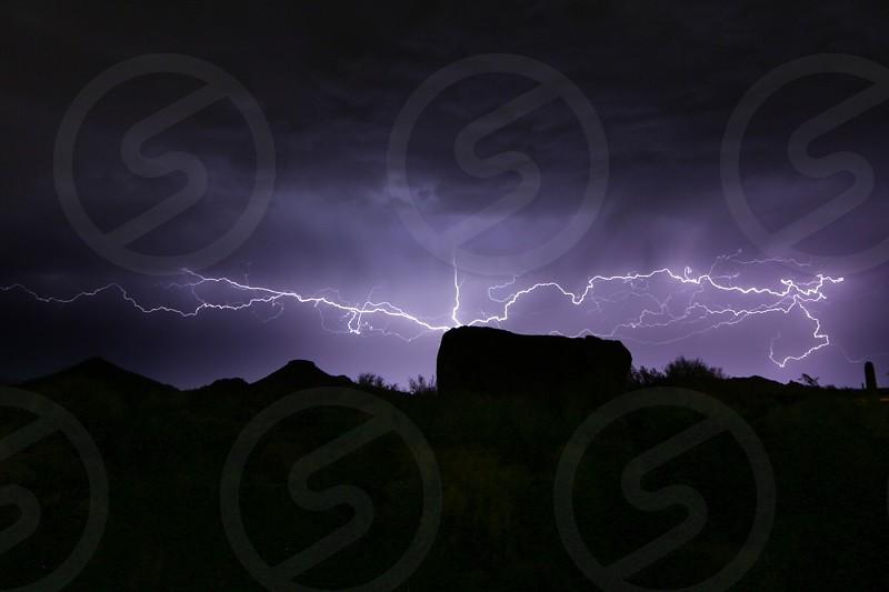 lightning striking on ground at night photo