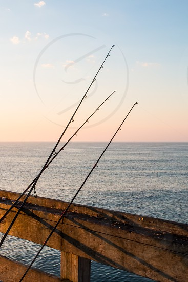 Three of a fisherman's fishing poles resting on a pier in early morning. photo