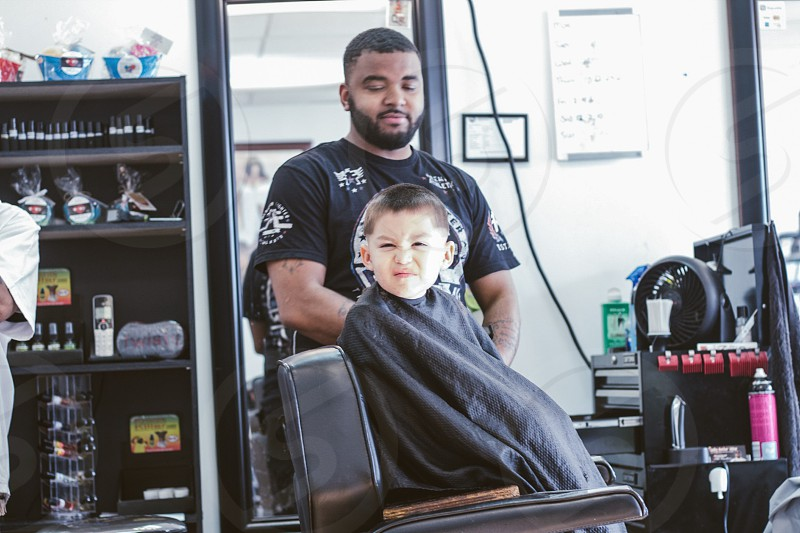 man beside a boy on barber's chair photo