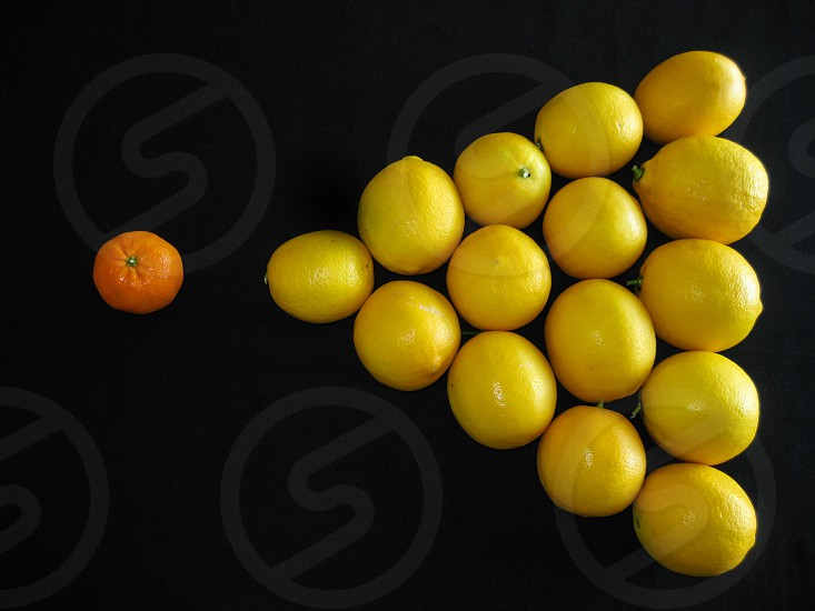 A tangerine poses as the cue ball in a billiard game using fresh citrus fruit with meyer lemons in a triangle against a black background for copy space. photo