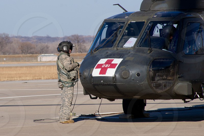 army pilot standing beside black helicopter photo