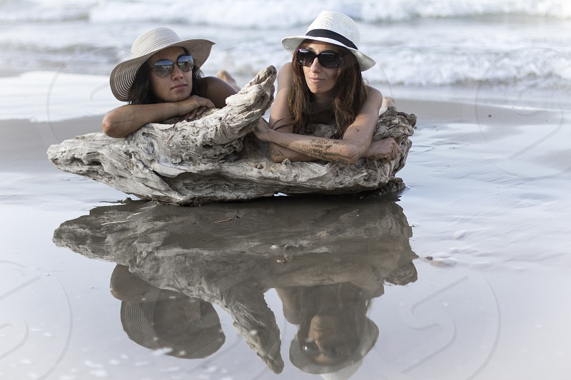 women laying on rocks on beach wearing white hats photo
