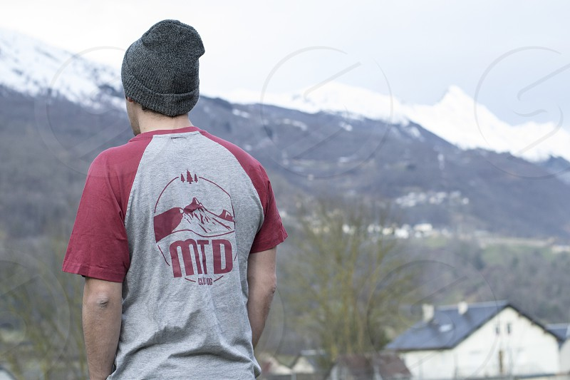 man in red and grey mtd shirt wearing grey beanie standing near white wooden building photo