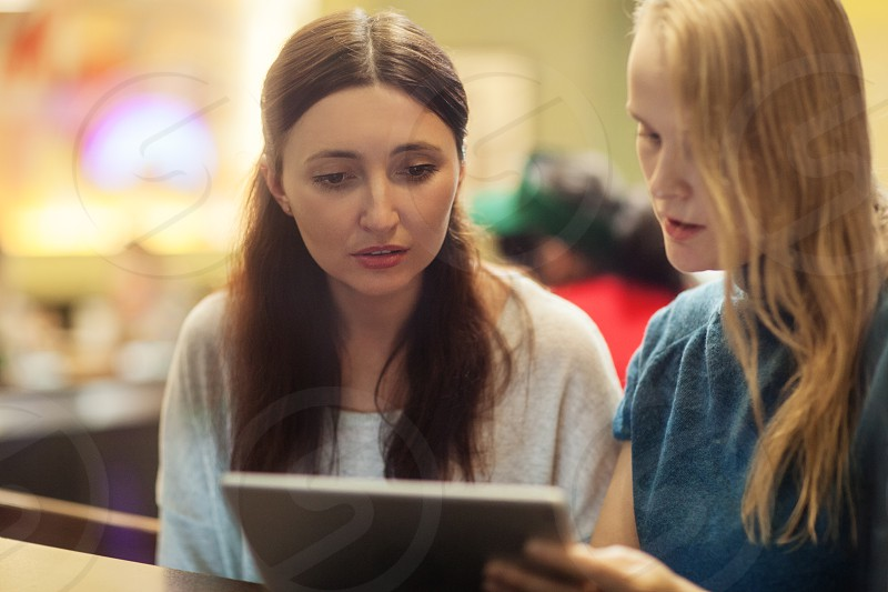 Serious blonde and brunette women talk in the restaurant watching something on the tablet photo