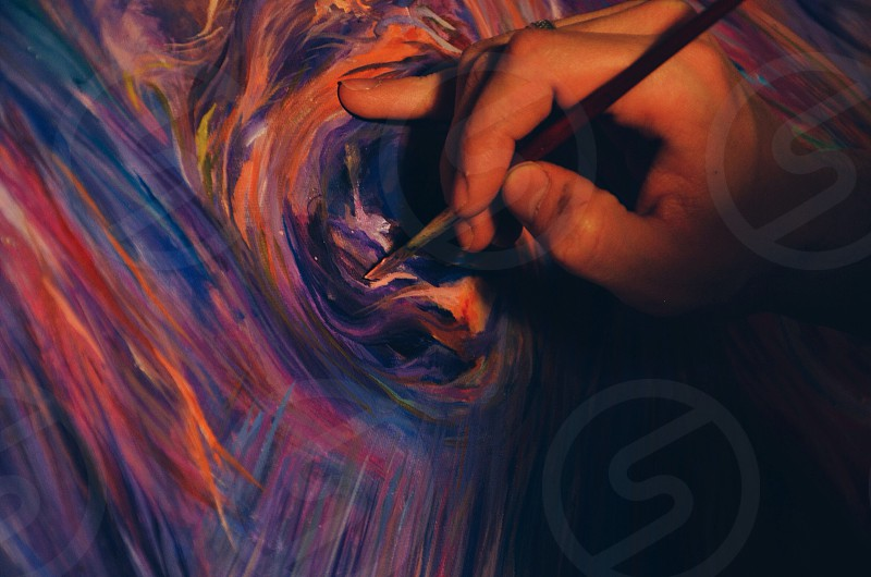 person painting an abstract image photo