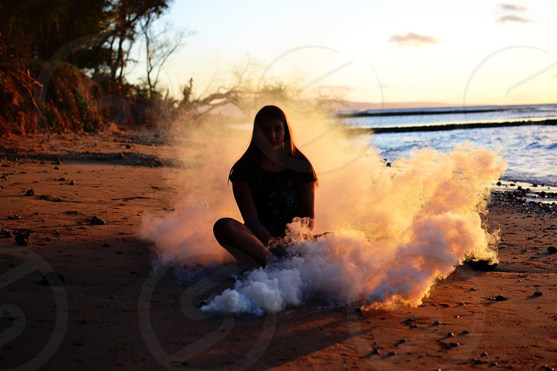 silhouetted girl surrounded by a smoke bomb on a beach photo