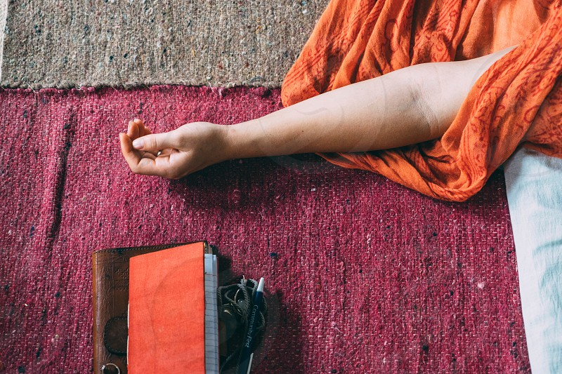 a woman in an orange scarf resting on a maroon carpet next to her orange journal.  photo