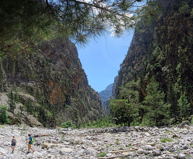 Samaria; Crete / GREECE May 25 2017: People hiking through Samaria Gorge in national park Lefka Ori mountains (Crete; Greece). They are resting on a wild stream. Pine trees around. made of 4 images. photo