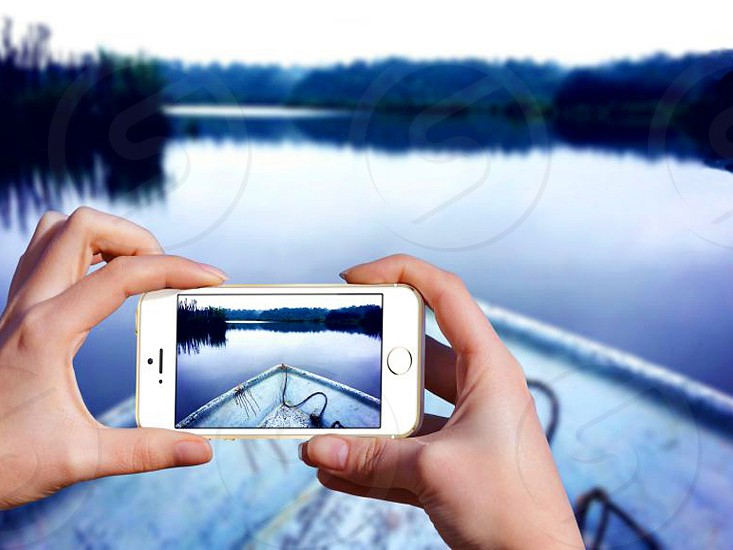 person take photo canoe and lake using silver iphone 5s during daytime photo