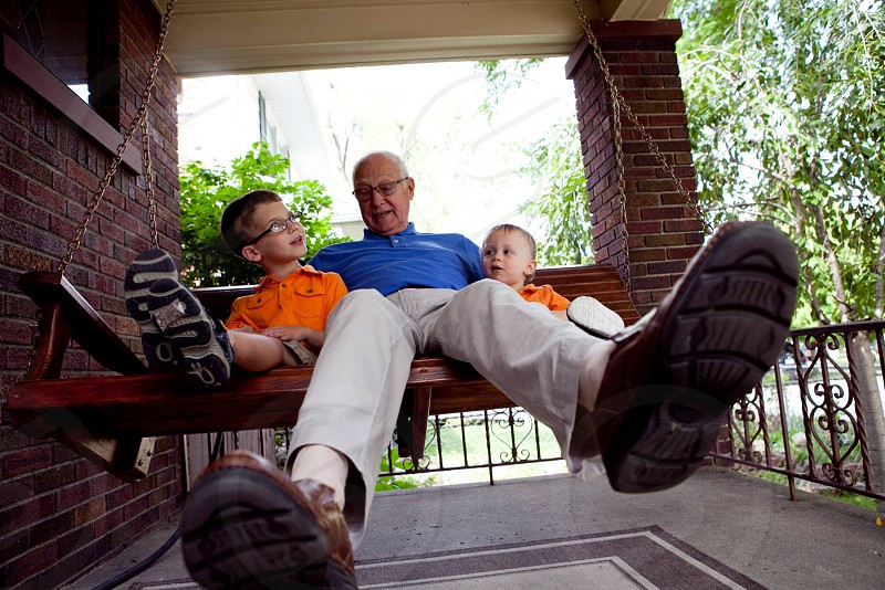 Great-grandpa swinging on porch swing with great-grandchildren  photo