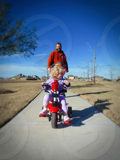 girl riding a trike with her father at her back under bright sky during daytime photo