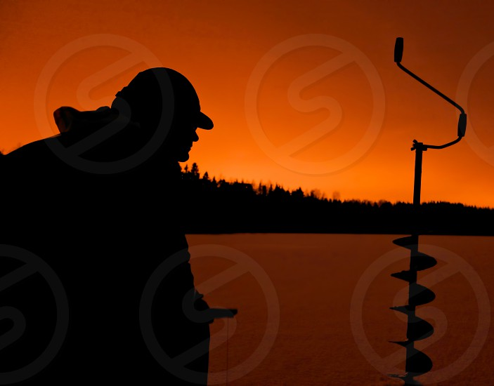 Silhouette of a ice fisherman. photo