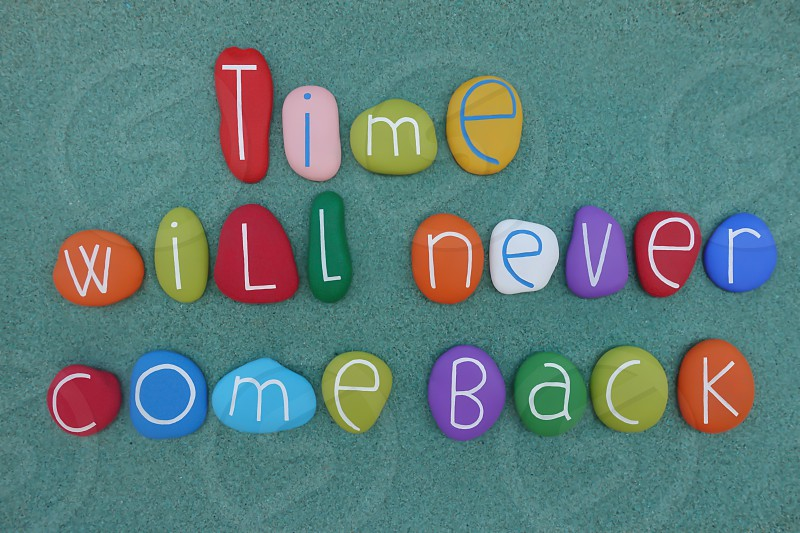 Time will never come back message composed with colored stones over green sand                     photo