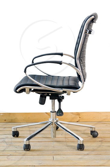 modern black leather office chair on wood floor over white background photo