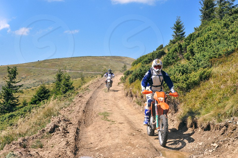 motorcyclists in helmets motocross in the mountains photo