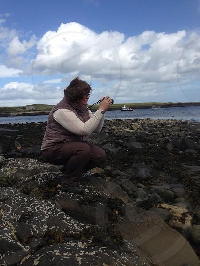 Woman on rocky Scottish beach taking photo with camera  photo