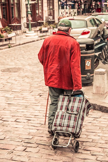 Elderly Man With Walking Stick And Shopping Cart In The Street photo