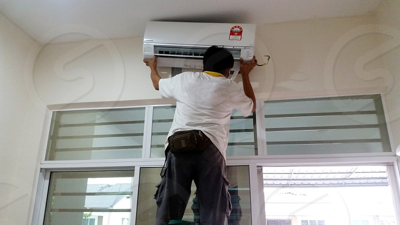 person in white shirt attaching split type airconditioner inside the room photo