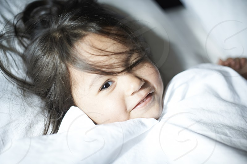 Close up of a cute Asian girl laying down on a bed and white pillow looking happy and contented photo