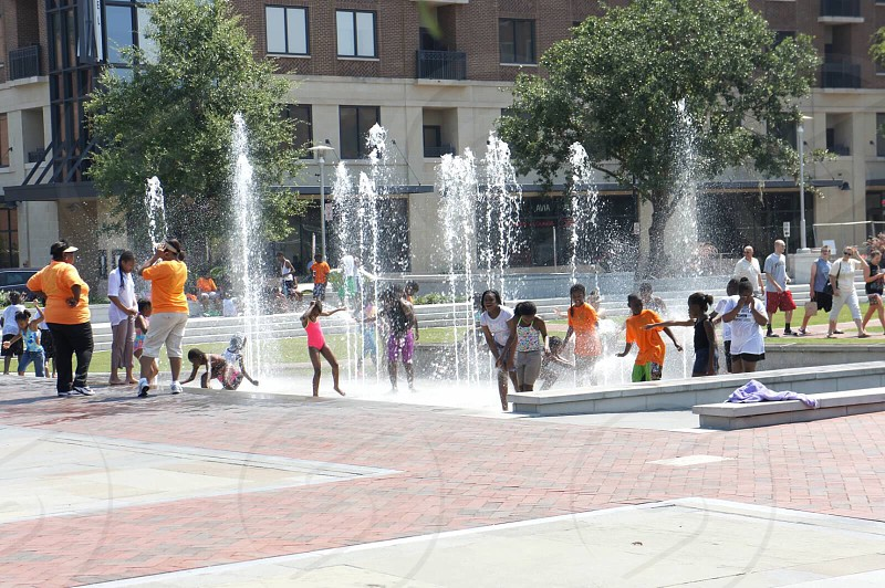 people playing in the fountain in a park with green trees during daytime photo