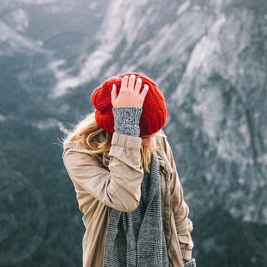woman in brown jacket standing while holding her red knit cap during daytime photo