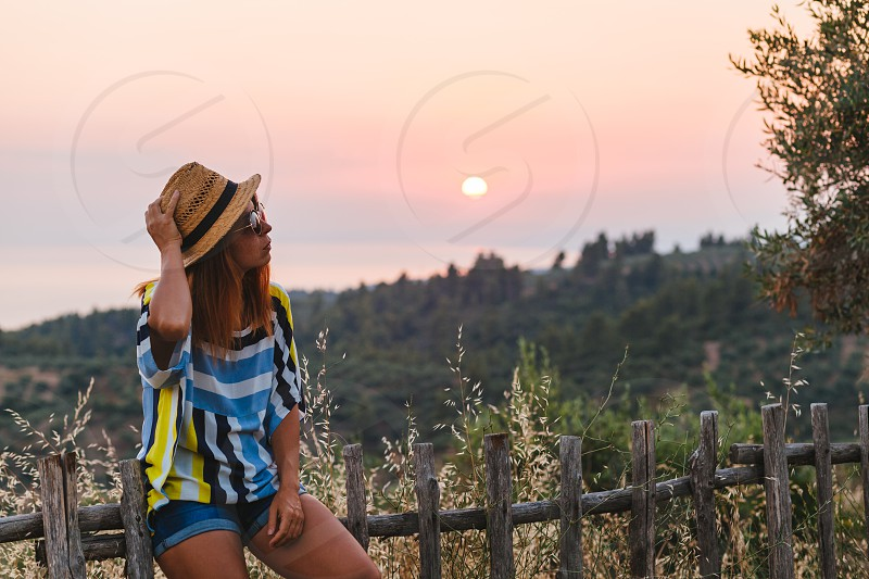 Young woman enjoying sunset view on the hill over the seaside photo